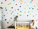 Adore the colorful polka dots wall with gold accents in the baby room | 10 Colourful Nurseries - Tinyme Blog